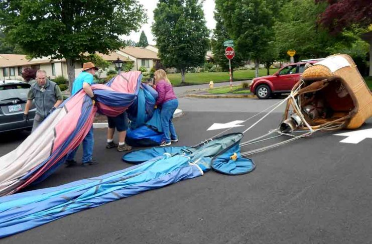"""After the inflated balloon was """"walked"""" across Summerfield Drive to the Clubhouse parking lot and deflated, the crew rolled up the balloon and stuffed it into a canvas bag"""