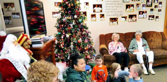 A Gentog staff member (center) leads a lesson in sign language to both seniors and pre-kindergartners at the inter-generational daycare that features daily interactions between the two groups.