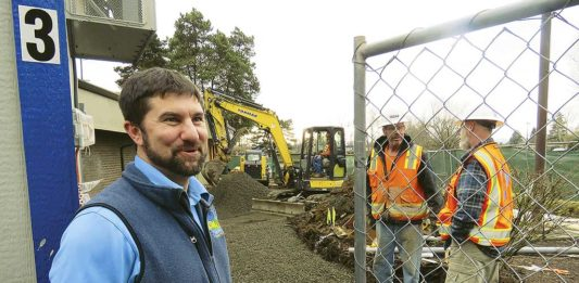 King City Manager Mike Weston chats with a city employee in the police parking lot while in the background, City Hall is undergoing a total transformation with construction slated to be completed in April.