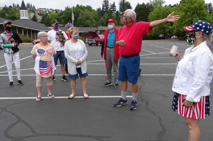 King City parade organizer Louis Martinez (in the red shirt) explains to parade participants the route they will take around the Golf Course.