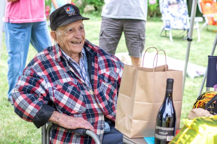 Paul Herberholz, relaxing under a canopy tent awaits the many visitors while receiving many gifts and cards.