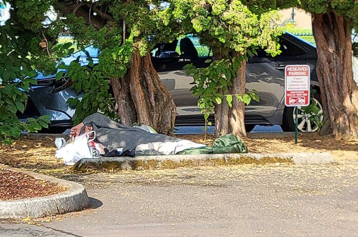 A homeless person sleeps in a downtown Tigard parking lot.