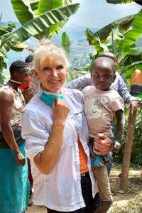 Dr. Julie Spaniel holds a child in Uganda.