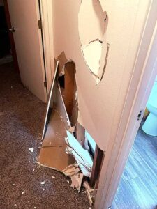 Police evidence photos show damage to an interior wall.